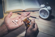 Some pills on male hand in night time. With book Stock Images