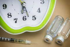 Some pills and red clock. Daily medication treatment Royalty Free Stock Photos