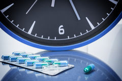 Some pills and red clock, daily medication treatment. Healtcare concept Stock Photography