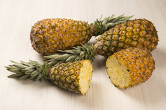 Some pineapples over a wooden table. Fresh fruit Stock Images