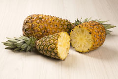 Some pineapples over a wooden table. Fresh fruit Royalty Free Stock Image