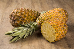 Some pineapples over a wooden table. Fresh fruit Royalty Free Stock Images