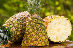 Some pineapples over a wooden table. Fresh fruit Stock Photography