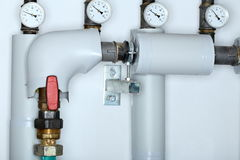 Some pipes. And thermometers in a heating room Stock Photos