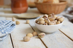 Some pistachios served on a bol on a white wooden table in a rustic kitchen. Royalty Free Stock Photos