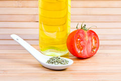 Some pizza ingredients. Three of pizza ingredients: olive oil, tomato and oregano in a spoon, on wooden background stock photo