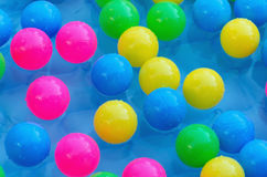Some plastic balls in a pool. Multi colored plastic balls on the water pool. Chilhood entertainment background royalty free stock photography