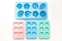Some plastic ice cube mold trays of different colors. A photo taken on some plastic ice cube mold trays with different colors against a white backdrop stock photo