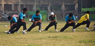 Young players stretching around a cricket ground. Some players are stretching around a green field isolated unique editorial photo royalty free stock photo