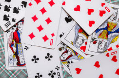 Some playing cards lays on a background of playing cards.  stock images