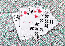 Some playing cards lays on a background of playing cards.  Stock Photography