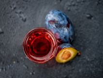 Some Plum Liqueur on a dark slate slab. Some Plum Liqueur on a vintage slate slab, selective focus Stock Photography