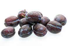 Some plums with drops of water. On the white background Stock Photos