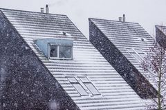 Pointy rooftops covered in snow during winter season, snowy weather, modern dutch architecture royalty free stock photos