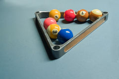 Some pool balls in the metal triangle ball rack on pool table.  stock image