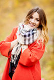 Some portraits of smiling girl, botanical garden, autumn look. Beautiful girl with a smile on her face in a red coat and a scarf in the park autumn day Stock Photos