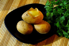 Some potatoes for holiday salad. On the black plate and parsley on the table Stock Photos