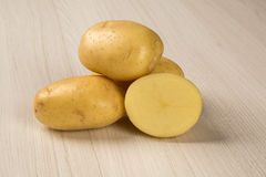 Some potatoes over a white background. Some potatoes over a wooden surface. Fresh vegetable royalty free stock photo