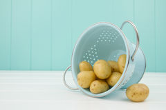 Some potatoes and a turquoise strainer Royalty Free Stock Images