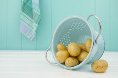 Some potatoes and a turquoise strainer Stock Photo