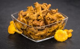 Some Preserved chanterelles on a dark slate slab. Portion of Preserved chanterelles on a rustic slate slab, selective focus, close-up shot royalty free stock photos