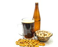 Some pretzels and pistachios with beer. On white royalty free stock image