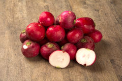 Some radishes in a basket over a wooden surface. Fresh vegetable Royalty Free Stock Images