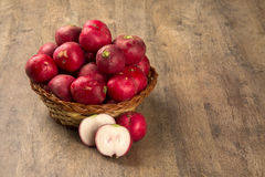 Some radishes in a basket over a wooden surface. Fresh vegetable Royalty Free Stock Photography