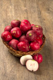 Some radishes in a basket over a wooden surface. Fresh vegetable Royalty Free Stock Image
