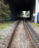Rails leading under overpass Stock Photo