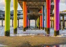 Rainbow colored stone poles under the pier of scheveningen beach the netherlands with sand and waves in the in the sea. Some Rainbow colored stone poles under royalty free stock images
