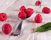 Some raspberry in metallic spoon. Closeup of ripe and fresh raspberries in metallic spoon and sprinkled on wooden desk Royalty Free Stock Image