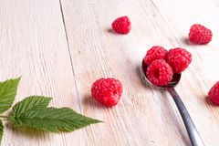 Some raspberry in metallic spoon. Closeup of ripe and fresh raspberries in metallic spoon and sprinkled on wooden desk Stock Photography