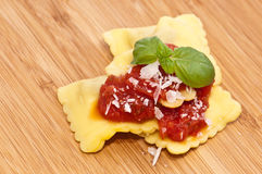Some Raviolis with tomato sauce. And Parmesan Cheese decorates with fresh basil on wooden background Royalty Free Stock Photos