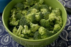 Some raw broccoli. Some fresh raw broccoli in a green bowl stock photo