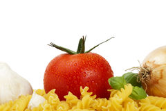 Some raw fusilli with tomato, onion, garlic and ba. Sil on white background Royalty Free Stock Photography