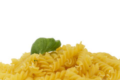 Some raw fusilli with wet basil. On white background royalty free stock image