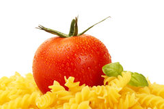 Some raw fusilli with wet tomato and basil. On white background stock photography