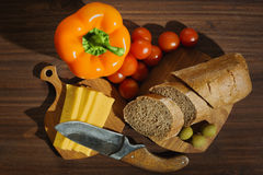 Some raw ingredients prepared for cooking. Brown baguette bread, yellow cheese, cherry tomatoes, bell pepper and olives on cutting boards with an old rural knife Royalty Free Stock Photo