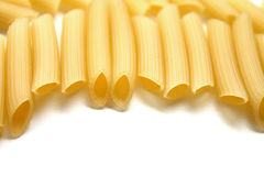 Some raw penne macaroni on white background. Close-up royalty free stock photos