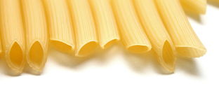 Some raw penne macaroni on white background Royalty Free Stock Photos