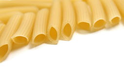 Some raw penne macaroni on white background. Close-up Royalty Free Stock Images