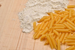 Some raw penne macaroni and white flour on a wooden rustic table Stock Image