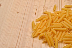 Some raw penne macaroni on a wooden rustic table. Healthy food. Selective focus royalty free stock photo