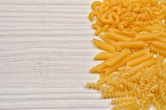 Some raw penne macaroni on a wooden rustic table. Healthy food. Selective focus stock photo
