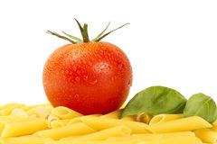 Some raw penne rigate with wet tomato and basil. On white background Stock Photography