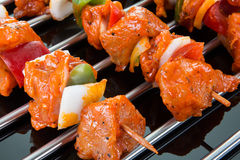 Some raw shaslik skewers on a cooking grate with reflections on. The black ground royalty free stock images