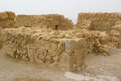 Some of the reconstructed ruins of the ancient Jewish clifftop fortress of Masada in Southern Israel. Everything below the marked. Blue lines is original stock images