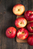 Some red apples on the board. Some red apples on the dark wooden table royalty free stock photos