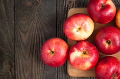 Some red apples on the board. Some red apples on the dark wooden table Stock Image